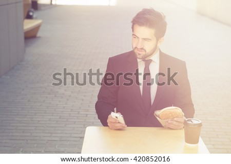 Toned picture of young confident businessman eating and drinkig in cafe. Handsome man sitting at table and looking away. - stock photo