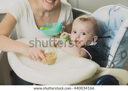 Toned portrait of beautiful baby boy eating porridge from spoon - stock photo