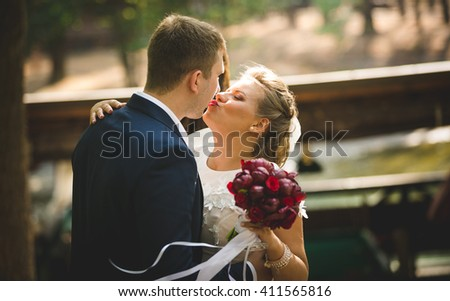 Toned portrait of beautiful bride and groom kissing at river - stock photo