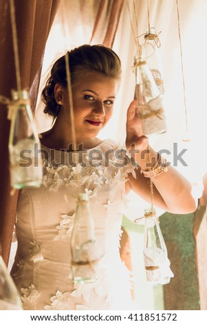 Toned portrait of beautiful bride posing with wedding decorations at restaurant - stock photo