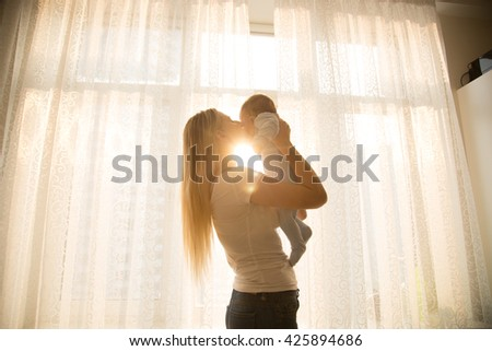 Toned portrait of cheerful mother holding her baby against big window  - stock photo