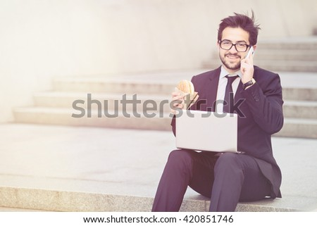 Toned portrait of handsome businessman in glasses looking at camera while working on laptop computer and eating hamburger. - stock photo