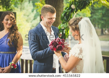 Toned portrait of happy newly married couple putting wedding rings - stock photo