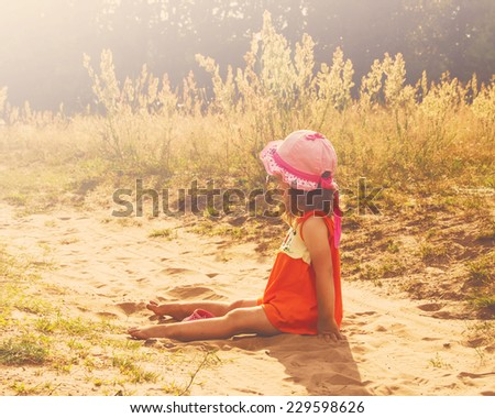 Toned portrait of little girl is sitting on sand in sunny day. - stock photo