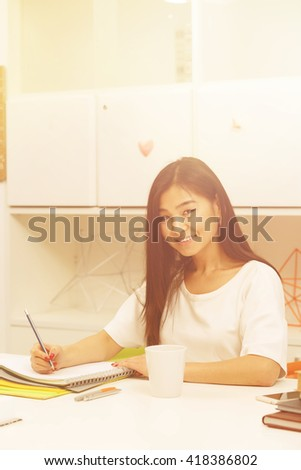 Toned  Portrait of pretty Asian student lady looking at camera and writing something in her exercise-book while studying in library. - stock photo