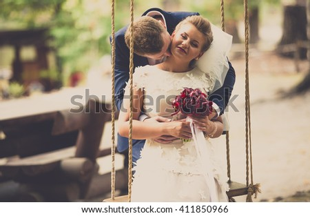 Toned portrait of young groom kissing bride sitting on swing at park - stock photo