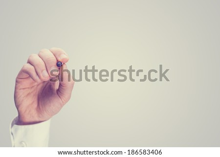 Toned retro image of the hand of a man writing on a blank virtual screen or interface with a marker pen with copyspace for your text or diagram. - stock photo