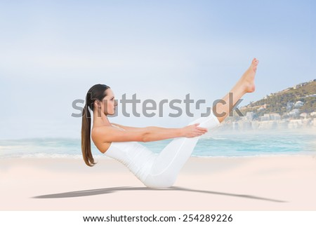 Toned woman doing the boat pose in fitness studio against beautiful beach and blue sky - stock photo
