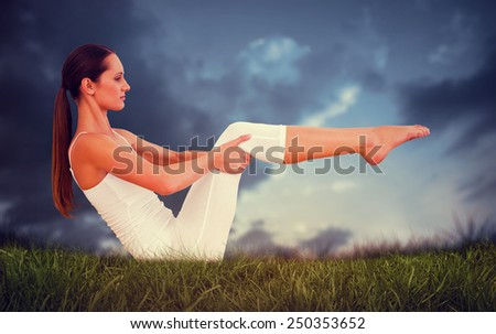 Toned woman doing the boat pose in fitness studio against blue sky over grass - stock photo