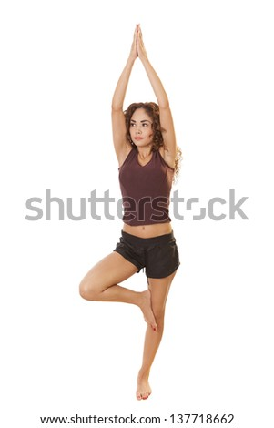 Toned woman stands on one leg during yoga, isolated on white background. - stock photo