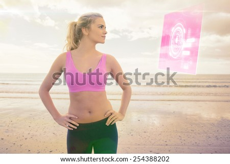 Toned woman with hands on hips on beach against fitness interface - stock photo