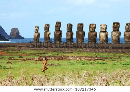 TONGARIKI, EASTER ISLAND - APRIL 1, 2009: Local man dressed in traditional costume looking for his horses in front of the most popular row of moais. - stock photo