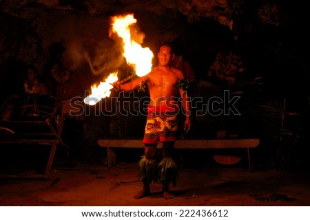TONGATAPU, TONGA - NOVEMBER 13: An unidentified man performs fire dance (blurred motion) in Hina cave on November 13, 2013 in Tongtapu, Tonga. Famous Hina cave is a big tourist attraction on Tongatapu