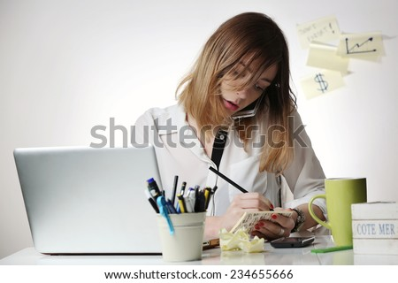Too busy, Young woman talking on mobile phone and writing notes while sitting at her desk. Pretty caucasian female working in home office. - stock photo