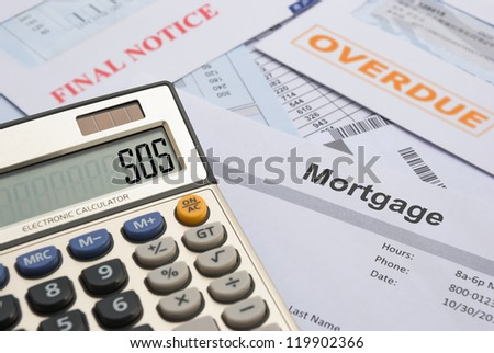 Too many bills and a calculator shows SOS, finacial concept - stock photo