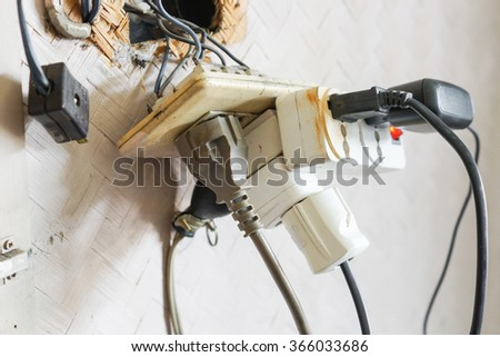 Too many plugs in a socket / Danger of using too much electricity - stock photo