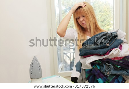 too much domestic work - too many clothes to iron and young exhausted and annoyed housewife at home - focus on pile of clothes to iron - stock photo