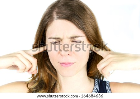 Too much noise: A young woman holds her hands over her ears to block out irritating sounds. - stock photo