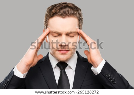 Too much stress. Frustrated young man in formalwear touching head with fingers and keeping eyes closed while standing against grey background