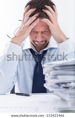 Too Much Work. Portrait of exhausted businessman sitting at office desk full with papers. - stock photo