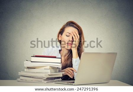 Too much work tired sleepy young woman sitting at her desk with books in front of laptop computer isolated grey wall office background. Busy schedule in college, workplace, sleep deprivation concept - stock photo