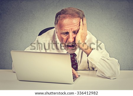 Too much work to do. Tired sleepy senior man sitting at his desk in front of laptop computer isolated on grey wall office background. Busy schedule in college, work place, sleep deprivation concept - stock photo