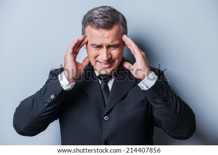 Too stressful day. Frustrated mature man in formalwear touching head with fingers and keeping eyes closed while standing against grey background - stock photo
