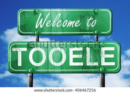tooele vintage green road sign with blue sky background