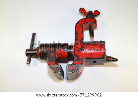 tool for work, vise painted with red paint, paint peeled, on white background