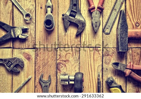 Tool frame. Wrench, ring spanner, hammer, flat file, pliers, screwdriver, monkey wrench on natural wooden background. - stock photo