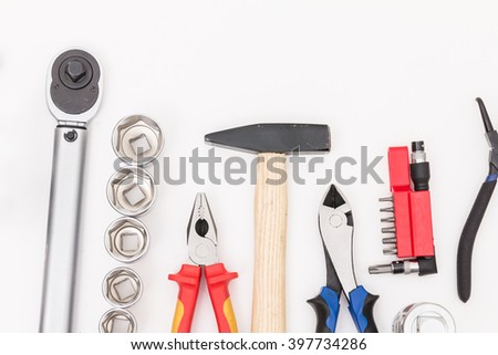 tooling on white background. A set of hardware tools: socket spanner, hammer, pliers, wire cutter - stock photo
