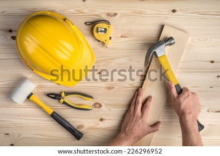 tools and hands working with hammer and helmet on wooden background - stock photo