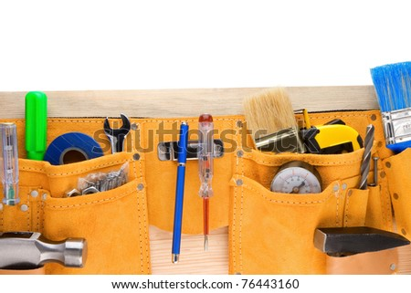 tools and instruments in belt isolated on wooden texture - stock photo