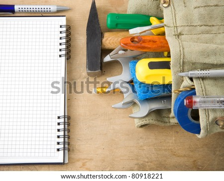tools and notebook on wood texture