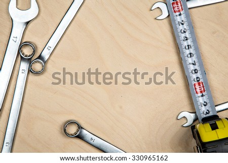 Tools and wrenches on the wood plate. Construction background with tools. - stock photo