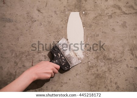 Tools, dirty spatula in hand on a concrete background, work plasterer, painter. Repair. Trowel in hand of man. Plastered walls. Space for text - stock photo