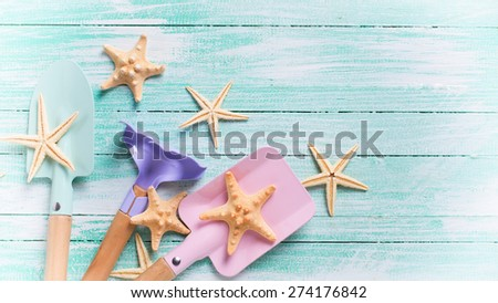 Tools for children for playing in sand  and sea object on turquoise  painted wooden planks. Place for text. Vacation, holiday, summer background. Toned image.  - stock photo