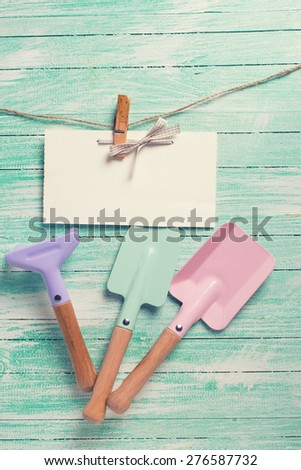 Tools for children for playing in sand and tag on clothes line on turquoise  painted wooden planks. Place for text. Vacation, holiday, summer background. Toned image.  - stock photo