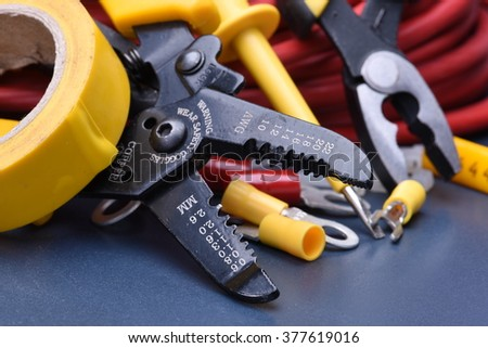 Tools for electrician and cables on metal surface - stock photo