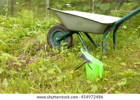 Tools for gardening. Rake, watering can and wheelbarrow on grass
