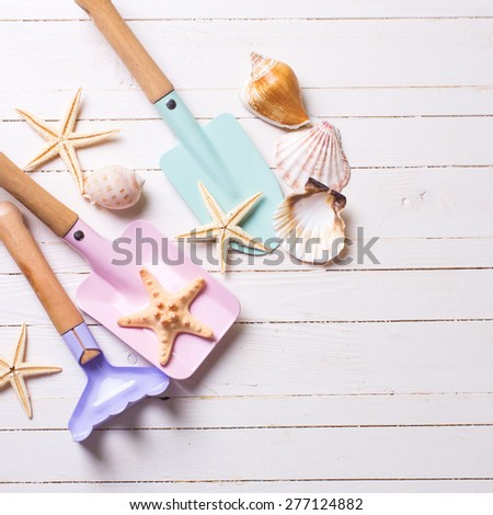 Tools for kids for playing in sand and sea object on white  painted wooden background. Place for text.  Square image. - stock photo
