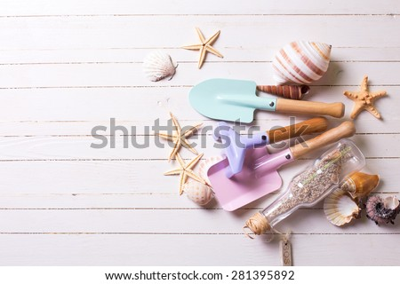 Tools for kids for playing in sand and sea object on white  painted wooden background. Place for text. Vacation background. - stock photo