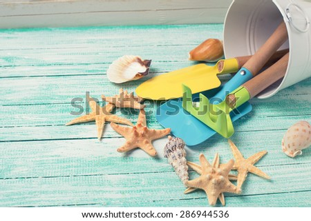 Tools for kids for playing in sand and sea objects on turquoise  painted wooden planks. Place for text. Vacation background. Toned image. - stock photo