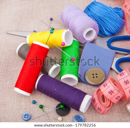 Tools for needlework, thread, scissors, pins, measure type and buttons on fabric