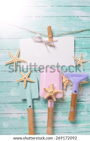 Tools for playing in sand  and sea object in ray of light on turquoise  painted wooden planks. Place for text. Vacation, holiday, summer background. - stock photo