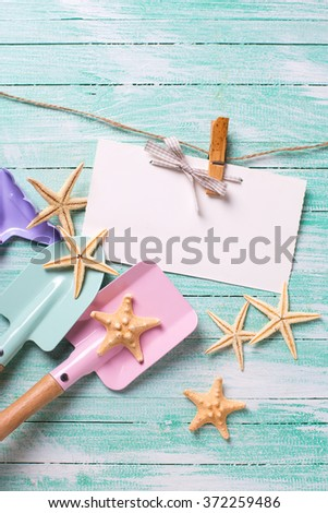 Tools for playing in sand  and sea object on turquoise wooden planks. Place for text. Vacation, holiday, summer background. - stock photo