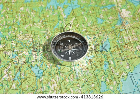 Tools for the journey - a map and a compass. Magnetic compass is located on a topographic map. - stock photo