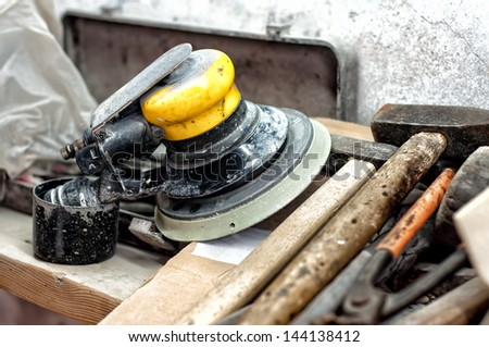 Tools in garage, hammer, screwdriver and power buffering machine used for polishing cars and metal surfaces - stock photo