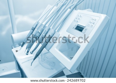 Tools of dentist in a dentist office. Blue tone. - stock photo