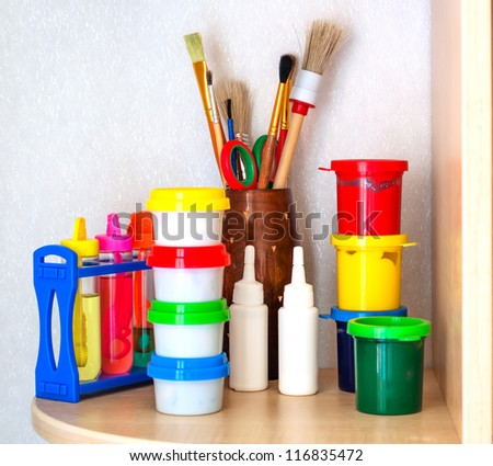 Tools of the artist: paints, brushes on a shelf in the children's room - stock photo